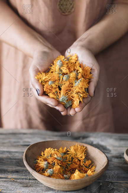 Woman with hands clasped holding fresh orange flowers over bowl on table