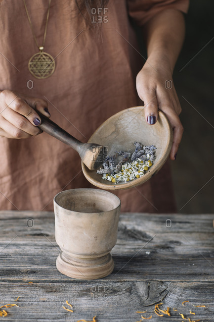 Midsection of woman putting flowers and herbs in mortar from earthenware bowl