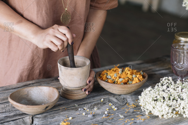 Midsection of woman crushing flowers and herbs in mortar with pestle on wooden table