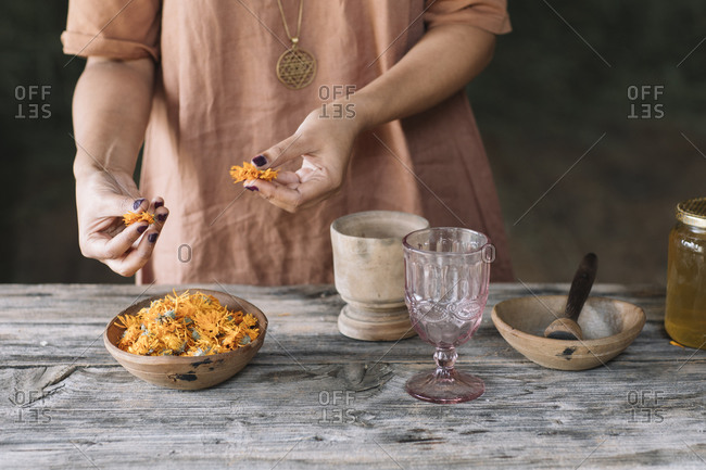 Midsection of mid adult woman choosing fresh orange flowers from bowl on wooden table
