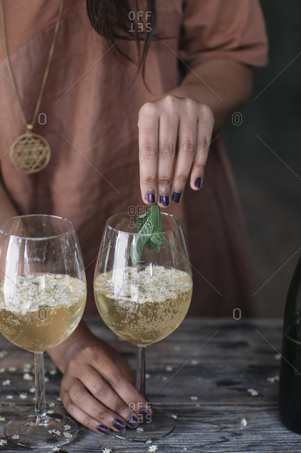 Midsection of woman holding mint leaves over wineglass while preparing cocktail