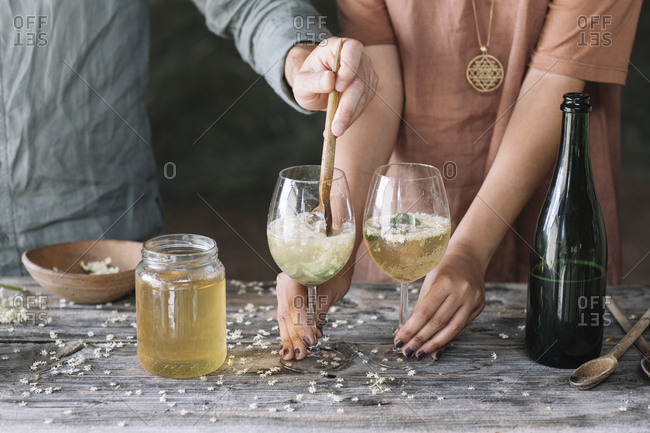 Midsection of man stirring wine in glass while preparing cocktail with girlfriend