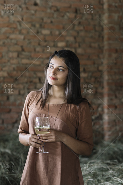 Thoughtful woman holding fresh cocktail while looking away against brick wall at barn