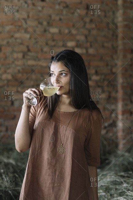 Thoughtful woman drinking fresh cocktail while looking away against brick wall at barn