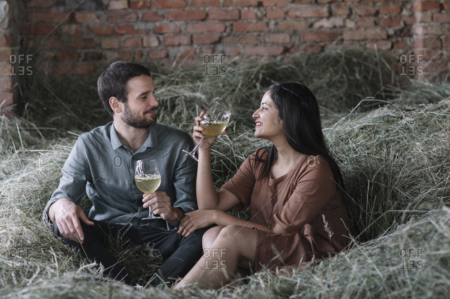 Happy couple with cocktails sitting on hay in barn