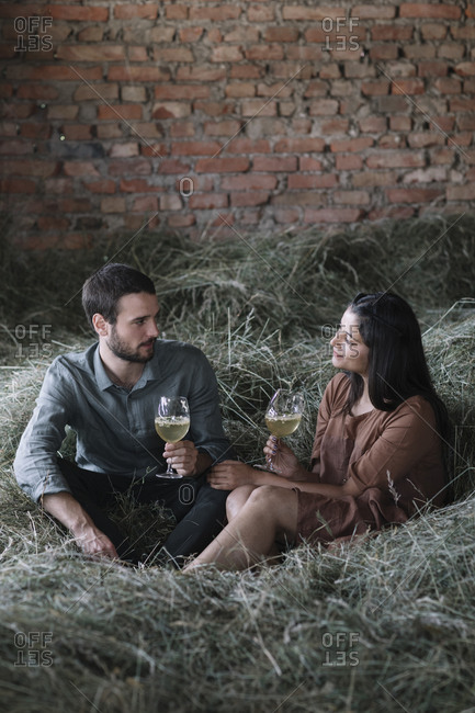 Multi-ethnic couple with cocktails sitting on hay against brick wall in barn