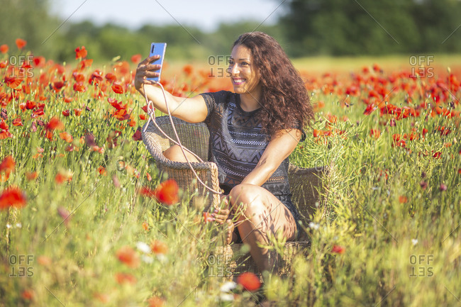 Smiling young woman taking a selfie sitting in basket-chair on poppy field