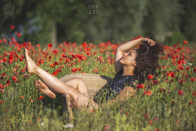 Young woman sitting in basket-chair on poppy field