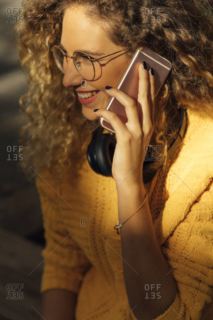 Smiling young woman looking away while talking on mobile phone