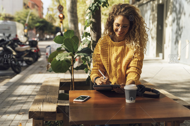 Smiling beautiful female student using digital tablet while sitting at sidewalk cafe in city