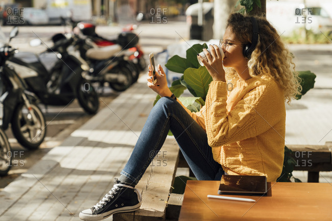 Young female student drinking coffee while using smart phone at sidewalk cafe in city