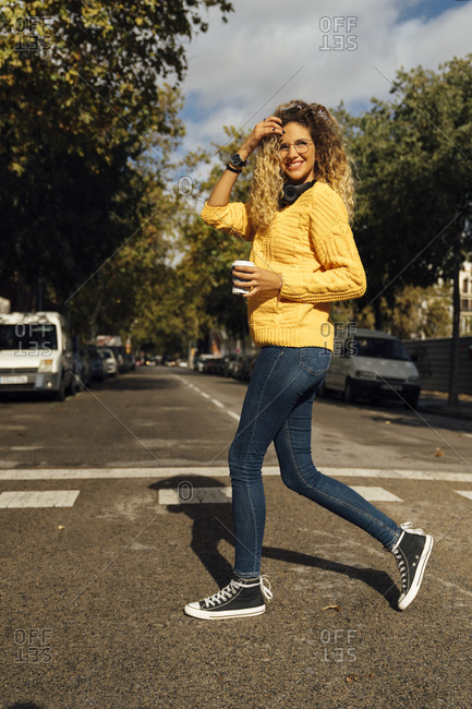 Smiling young woman crossing street while walking with disposable cup in city on sunny day