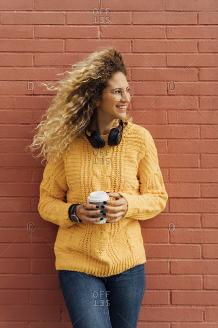 Beautiful young blond woman with long curly hair looking away while holding disposable coffee cup against red brick wall
