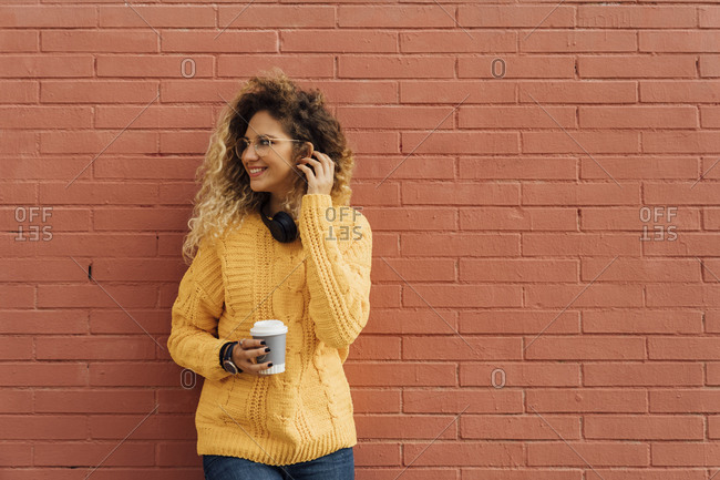 Smiling female student with long curly hair looking away while holding disposable coffee cup against red brick wall