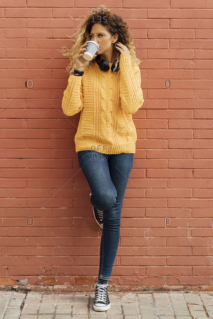 Beautiful young woman looking away while drinking coffee from disposable cup against red brick wall