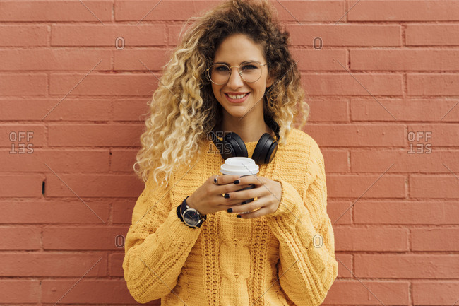 Happy young female student with long curly blond hair holding disposable coffee cup against red brick wall