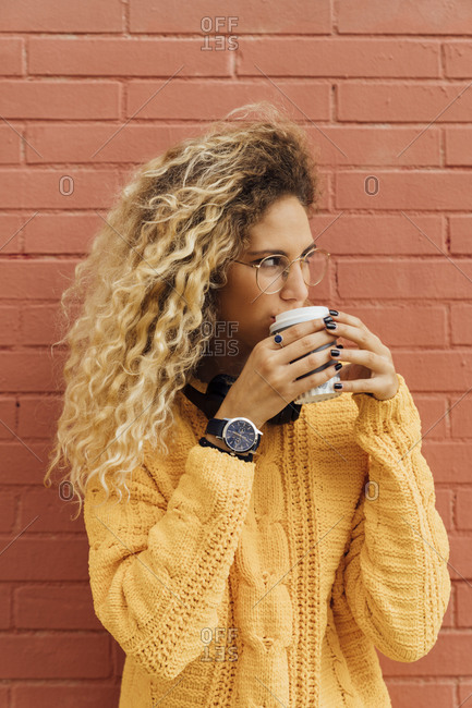 Young woman drinking coffee from disposable cup while looking away against red brick wall