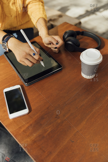 Midsection of young female student using digital tablet at sidewalk cafe table