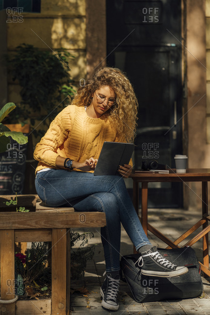 Young blond woman using digital tablet while sitting at sidewalk cafe in city