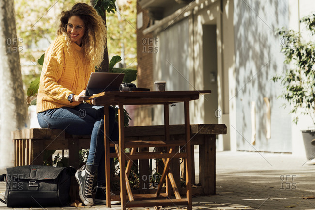 Cheerful young woman looking away while sitting with digital tablet at sidewalk cafe in city