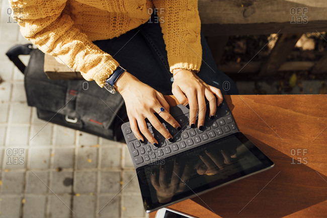Midsection of female student typing on digital tablet keyboard while sitting at sidewalk cafe in city