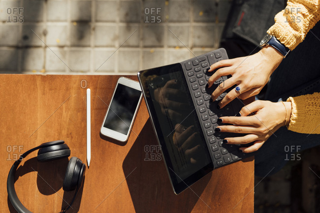 Hands of female student typing on digital tablet keyboard while sitting at sidewalk cafe in city