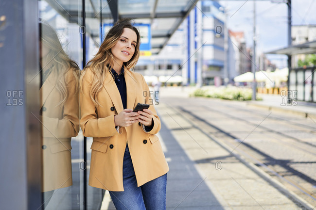 Beautiful woman looking away while waiting at tram station