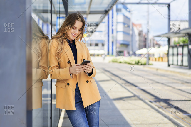 Smiling woman using smart phone while waiting at tram station