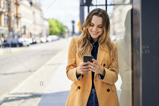 Smiling woman text messaging through smart phone while waiting at tram station
