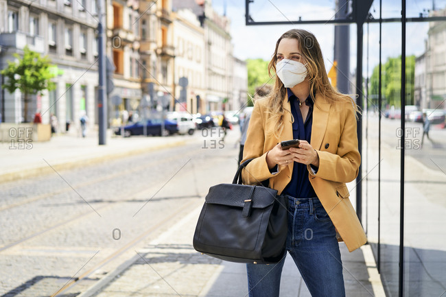 Woman wearing protective face mask while waiting at tram station during COVID-19