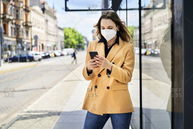 Woman in protective face mask using smart phone while waiting at tram station