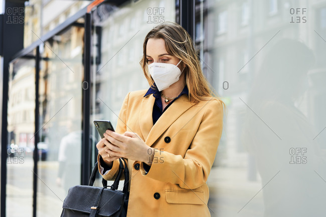 Woman in protective face mask using smart phone while waiting for public transportation