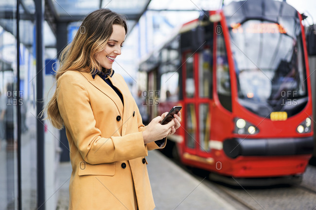 Woman text messaging through smart phone while waiting at tram station
