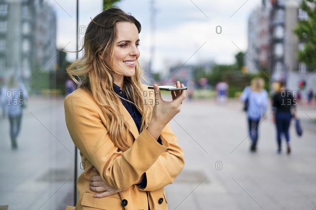 Smiling woman using speaker while talking through smart phone at tram station