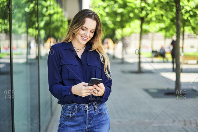 Smiling beautiful woman text messaging through smart phone while standing on footpath in city
