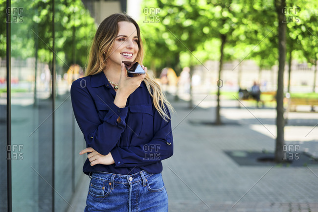 Smiling woman looking away using speaker while talking through smart phone