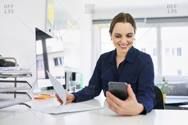 Creative businesswoman using smart phone while doing paperwork in office