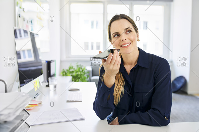 Businesswoman using speaker while talking on smart phone at desk in office