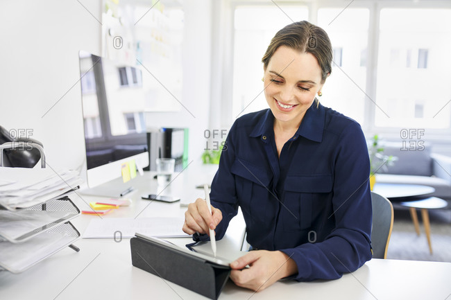 Smiling creative businesswoman using digital tablet at desk in office