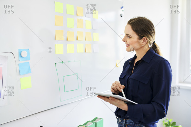 Smiling businesswoman with digital tablet looking at sticky notes stuck on whiteboard in office