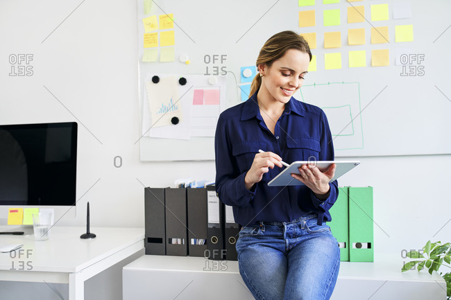 Smiling creative businesswoman using digital tablet while leaning on desk in office