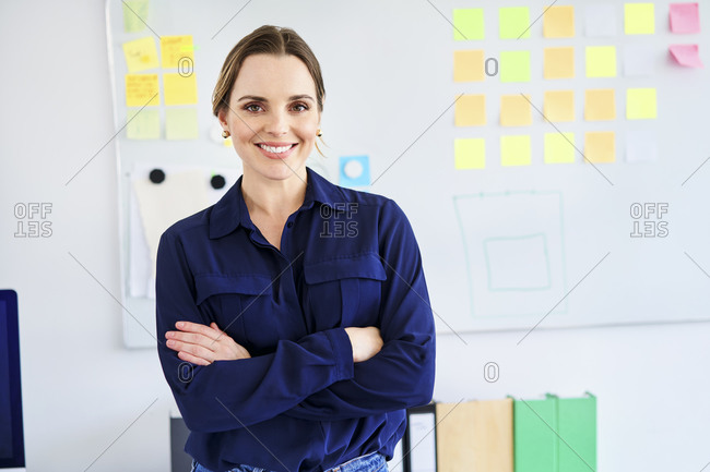 Confident businesswoman standing with arms crossed in creative office
