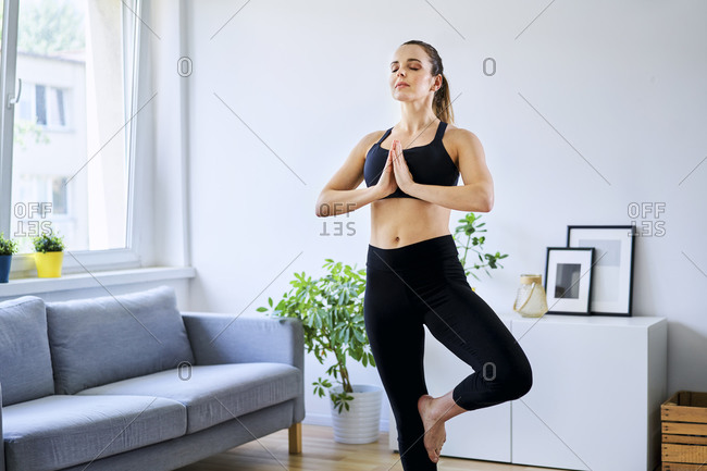 Woman practicing tree pose with eyes closed in living room