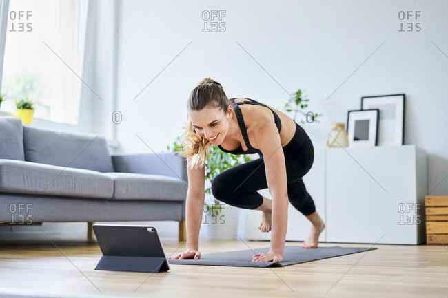 Smiling woman learning exercise on internet through digital tablet at home
