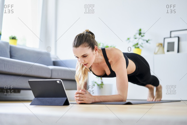 Woman learning plank exercise on internet through digital tablet at home