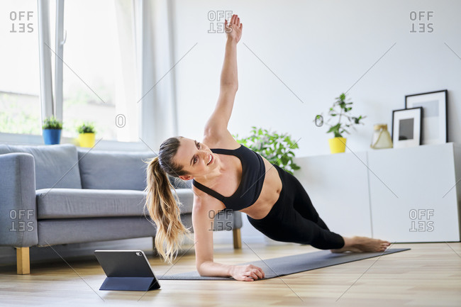 Woman doing side plank exercise in living room at home