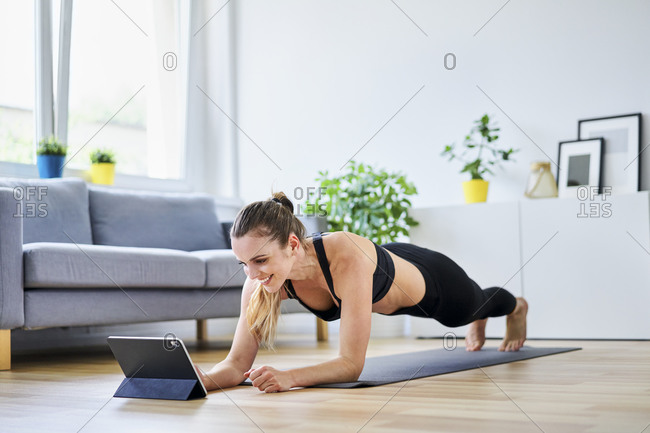 Smiling woman learning plank exercise on internet at home
