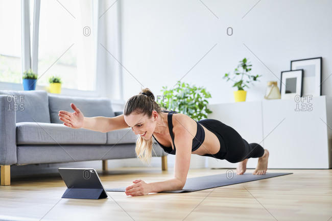 Woman extending arm during plank pose while learning exercise on internet through tablet PC