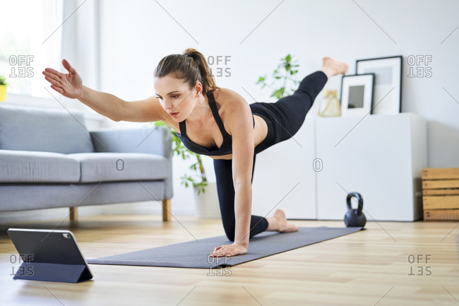 Determined woman learning home workout through internet on digital tablet
