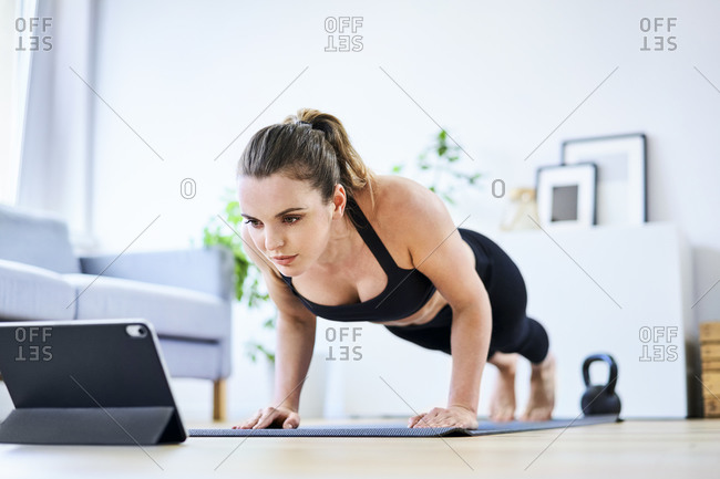 Woman learning exercise on internet through tablet PC at home